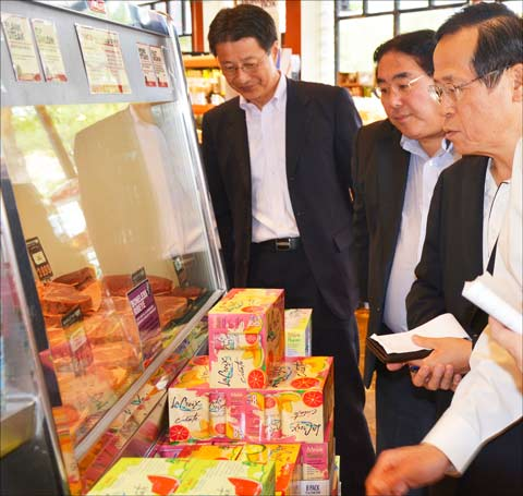 At Marczyk Fine Foods, a neighborhood grocery in Denver, ALIC officials examine how beef and pork cuts are presented. (L. to r.) Hiroyuki Kobayashi, ALIC chief executive director; Takemichi Yamashoji, USMEF Japan director; and Wataru Miyasaka, ALIC president