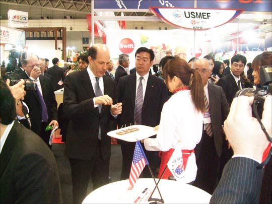 John V. Roos (left), U.S. Ambassador to Japan, samples U.S. pork and beef at USMEF's FoodEx booth