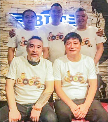 """BLT staff show off the special T-shirts that read """"no meat, no joy"""" in Chinese"""