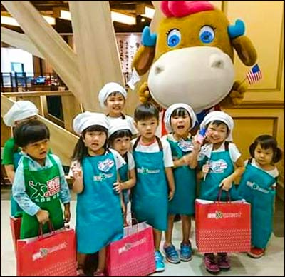 Taiwanese children gather for a photo with Baby Cow, the U.S. beef mascot, during a promotion at an Amart outlet