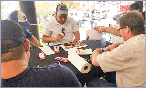 Judges sample U.S. pork St. Louis ribs prepared and grilled by a team of Costa Rican cooks in the Barbecue Fest grilling competition