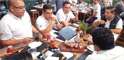 Employees of importer Belca Guatemala sample U.S. pork during a cutting and cooking demonstration