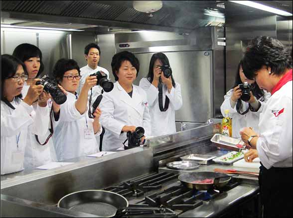 Korean bloggers watch and take photos as a USMEF chef cooks