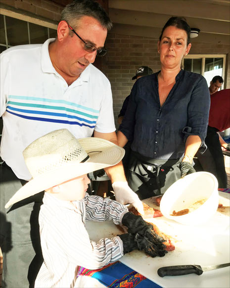 A young cowboy assists members of the chef team at the hands-on session at Boots Ranch