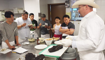 Bryan Bracewell, right, a Texas barbecue pitmaster, demonstrates methods of cooking U.S. beef and provides samples of slow-cooked barbecue to Korean chefs and food bloggers as part of a USMEF promotion