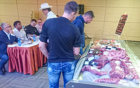 Romanian foodservice professionals inspect a cooler full of alternative cuts at a U.S. beef master class in Bucharest