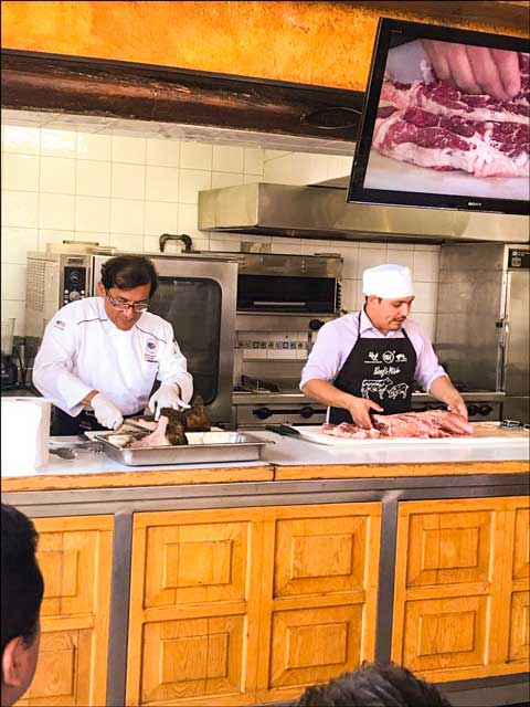 USMEF Chef German Navarrete (left) and consultant Luis Pachuca present an interactive U.S. pork and beef cutting and cooking demonstration in Puebla, Mexico