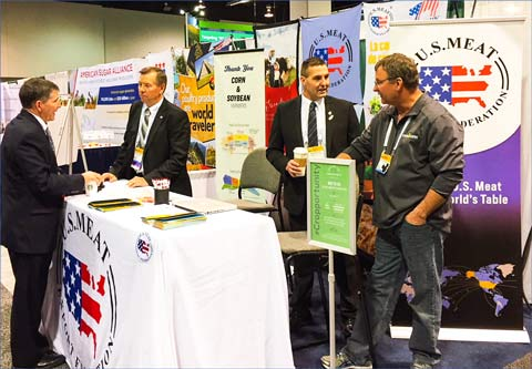 USMEF past chair Bruce Schmoll (second from left) and USMEF Executive Committee member Dean Meyer (third from left) answer questions from visitors to the USMEF booth at Commodity Classic
