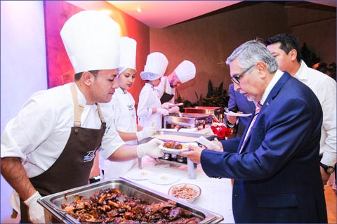 "An Ecuadorean guest samples appetizers at the ""Surf and Turf"" reception at the U.S. Embassy"