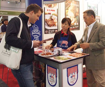 (left to right) A buyer at Fine Food Australia receives product information from Feon Wong of USMEF and S.G. Lee of Sugardale Foods