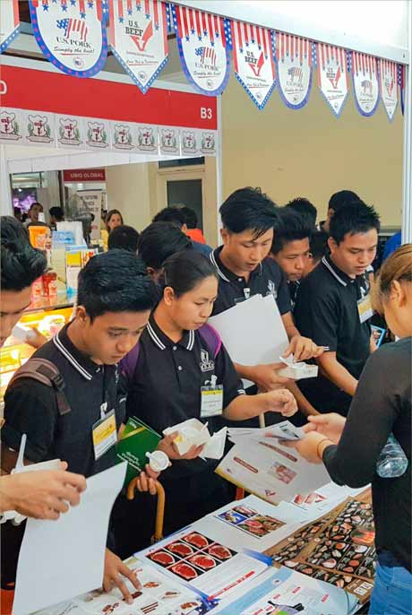 Visitors to the USMEF booth at Food and Hotel Myanmar are given educational information on U.S. pork and beef