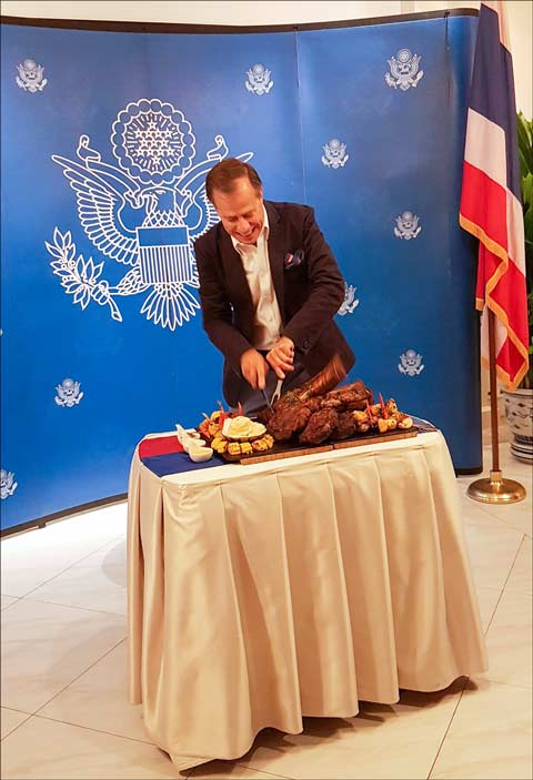 Glyn Davies, U.S. Ambassador to Thailand, carves U.S. bone-in beef at a ceremony marking the return of the product to the country