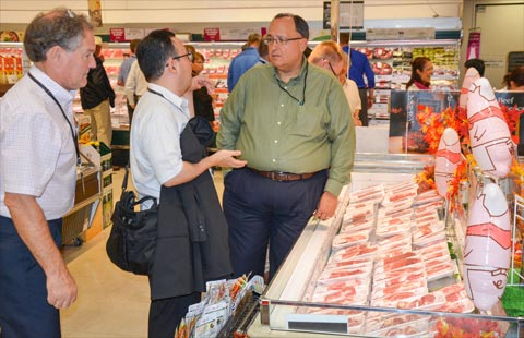Greg Krissek (right) of the Kansas Corn Commission discusses a retail display for U.S. pork