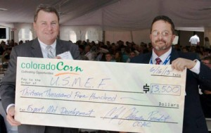 John Hinners (left) accepts a contribution from the Colorado Corn