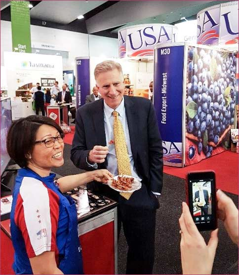 Sabrina Yin, left, USMEF ASEAN director, offers samples of U.S. pork to James Carouso, chargé d'affaires at the U.S. Embassy in Canberra, Australia.