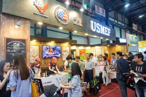 Visitors to the Korea Franchise Business Expo gather around the USMEF exhibit for samples of U.S. beef and pork