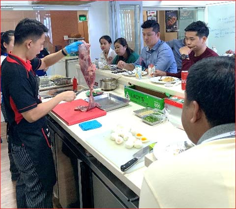 USMEF's Lawrence Char conducts cutting and cooking demonstrations for a team of Cambodian chefs