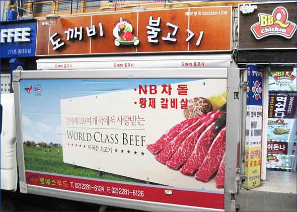 A delivery truck with world class beef ad unloads at a Seoul restaurant