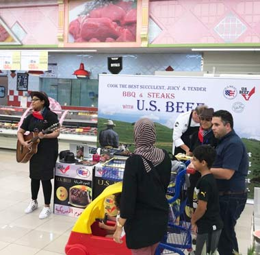 A musician performs country music at the USMEF display booth as shoppers learn about U.S. beef