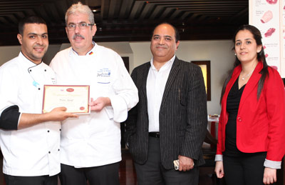 Chef Uwe Micheel (second from left) presents a certificate of completion to an Egyptian chef as Alaa Kamal of Midamar and Eliane Elia, USMEF Middle East representative, look on