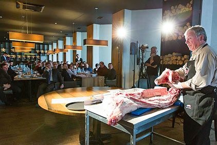 USMEF representative Monty Brown demonstrates the handling and cutting of a carcass at a U.S. pork seminar in Kiev, Ukraine