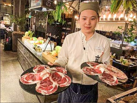 A chef at QiMin, a Taiwanese catering company with three outlets in Shanghai, poses with U.S. beef cuts at a hotpot event celebrating the company's one-year anniversary of serving U.S. beef