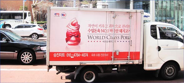 A truck with world class pork ad travels down Seoul street