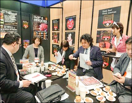 Representatives of supermarket chains and other retail outlets in Japan sample U.S. pork and beef at USMEF's Supermarket Trade Show booth