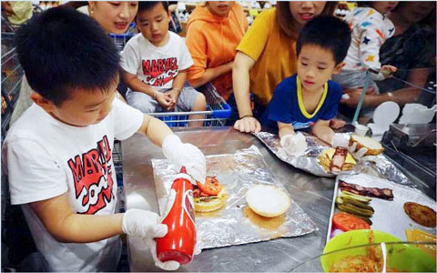 With instruction by a USMEF chef, a youngster puts the final touches on his entry at a burger making contest at a Shanghai Sam's Club