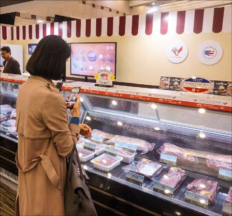 A buyer snaps a photograph of U.S. chilled pork and beef at the Samsung Welstory Food Festa