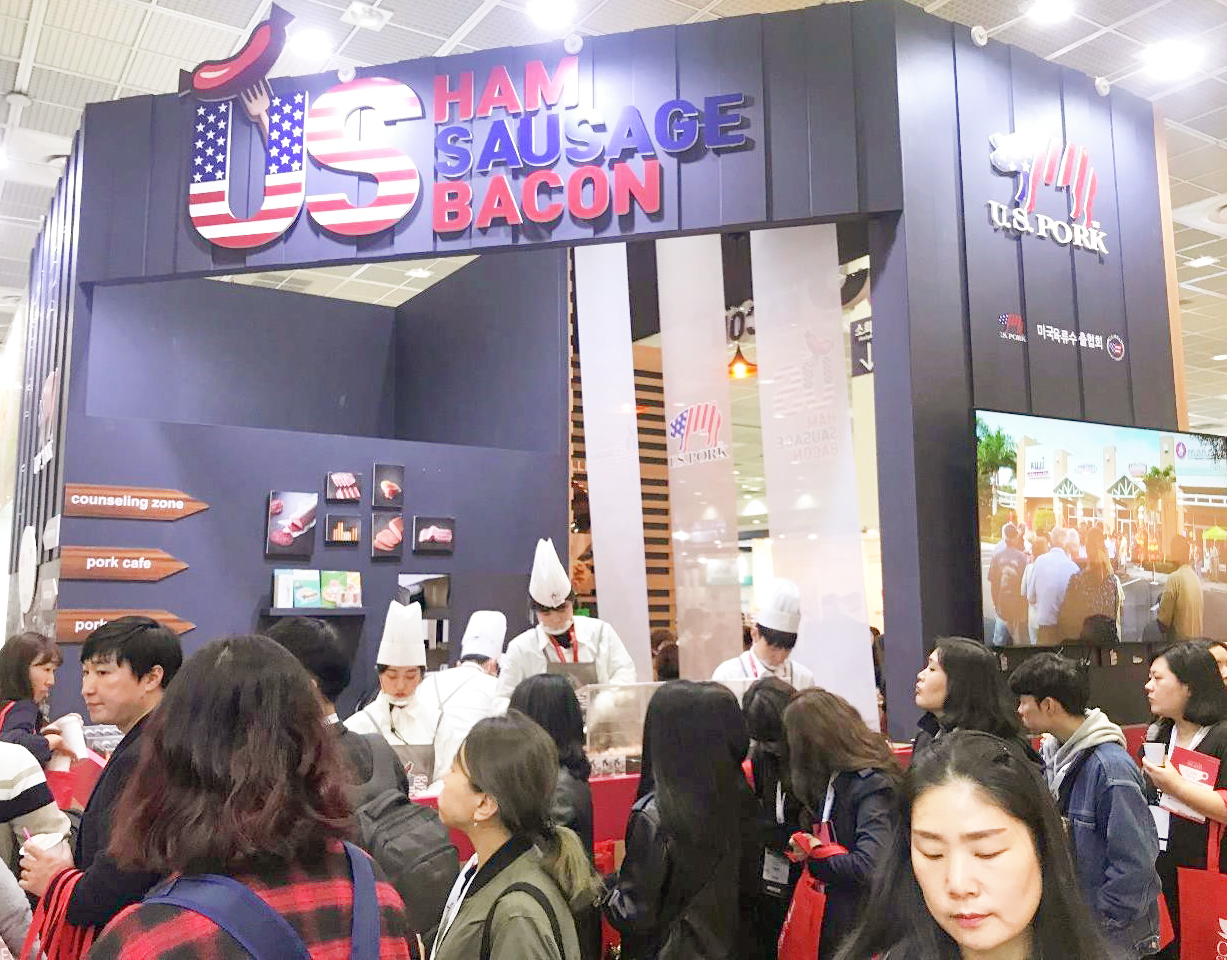 Attendees at the Seoul Cafe Show line up at the USMEF booth to learn about U.S. processed pork products and sample U.S. pulled pork, ham, sausage and bacon