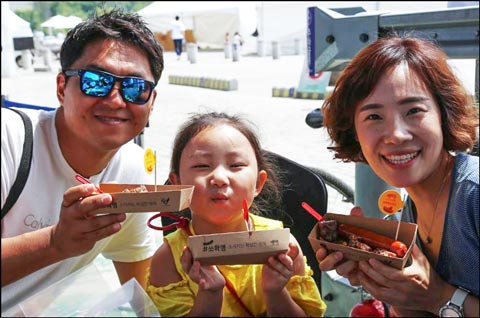 """A Korean family enjoys samples of U.S. pork sausages at the """"Picnic on the Bridge"""" event at the Seoul Food Festival"""
