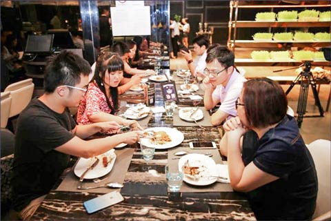Consumers in Shanghai share a U.S. pork dish at a tasting dinner at USMEF's second annual U.S. Pork Foodies Festival