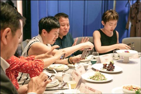 Chinese reporters snap photos before sampling U.S. beef and pork paired with Chinese tea at a USMEF media reception in Shanghai