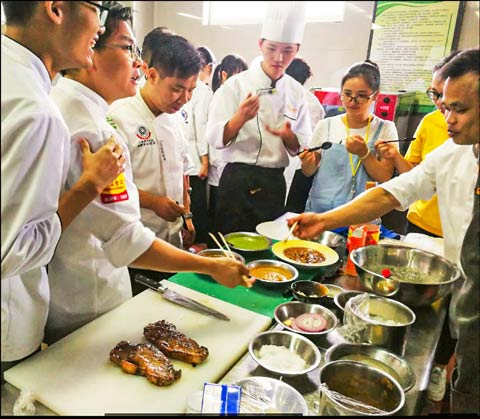 """Culinary instructors in Guangzhou, China, gather around a U.S. beef and pork cooking demonstration held during a """"train the trainer"""" program hosted by USMEF and the USDA Agricultural Trade Office"""