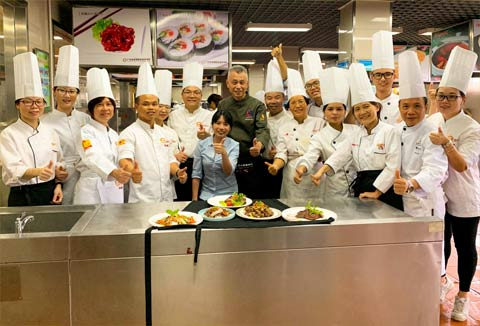 "Some of the culinary instructors participating in the ""train the trainer"" program pose for a group photo with dishes they prepared using U.S. beef and pork"