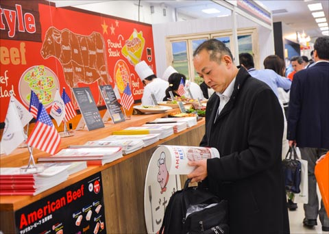 At the Yakiniku Business Fair in Tokyo, participants pick up informational materials on U.S. beef and pork at the USMEF display booth