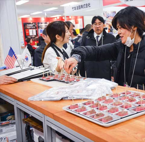 A visitor samples U.S. beef pound steak – a product promoted during the Yakiniku Business Fair – at the USMEF display booth