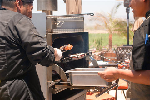 Cuts of U.S. beef and pork are pulled from a grill for tasting by seminar participants in Ensenada