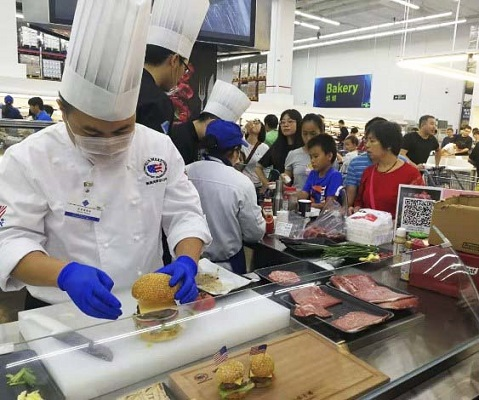 A chef at the U.S. Beef Burger Festival in Shenzhen prepares mini burgers and classic American hamburgers for Sam's Club shoppers
