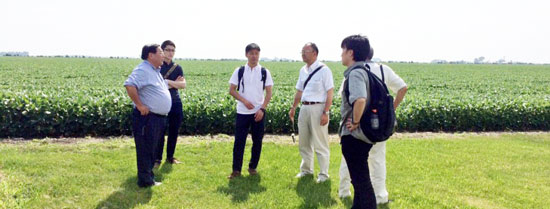 Takemichi Yamashoji (far left), USMEF senior marketing director in Japan, discusses U.S. agriculture as he leads a team of chefs from Japan's Prince Hotel and Resorts on a farm tour in Minnesota