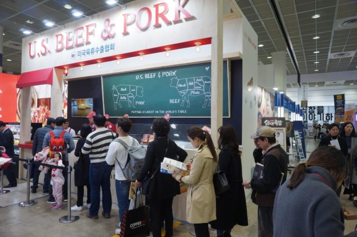 Visitors to the International Franchise Seoul exhibition stand in line to sample U.S. pork and beef dishes at the USMEF display booth