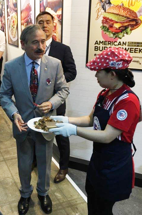 Harry Harris, U.S. ambassador to South Korea, samples U.S. beef chuck eye roll at the USMEF booth